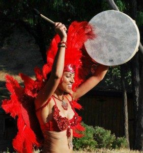 an image of a woman wearing a red feather costume playing a drum