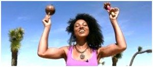 a curly haired woman wearing a pink blouse holding a wooden intrument in her both hands while lifting